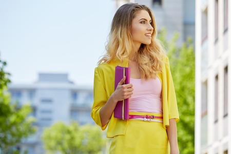 donna ricca: Beautiful blonde young woman wearing yellow dress walking on the street