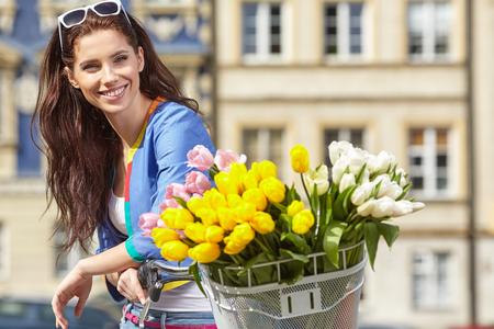 Blije modieuze vrouw in grijze hoed op een fiets met de lentebloemen op de achtergrond van de stad
