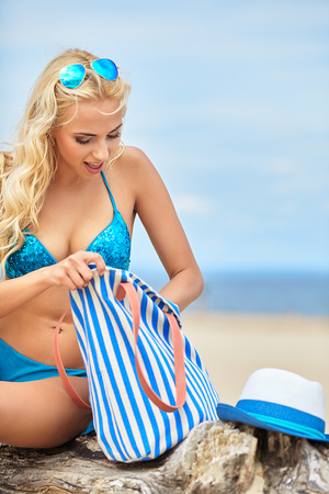Caucasian woman: summer holidays, vacation and beach concept - girl in bikini and shades on the beach