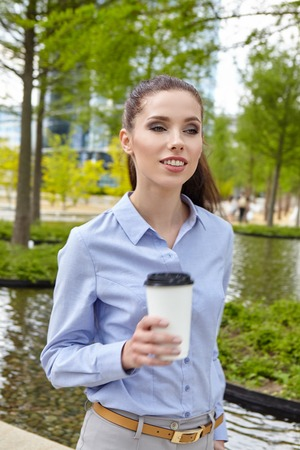 woman business suit: Young stylish business woman drinking coffee in a park at summer day.