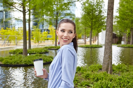 woman sunset: Young stylish business woman drinking coffee in a park at summer day.