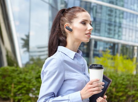 woman in office: Businesswoman Walking On Street and Holding hot coffee