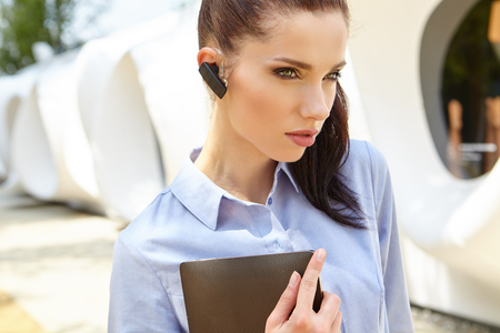 commercial building: Attractive young woman drinking coffee and reading her touchscreen tablet while standing outside a commercial building