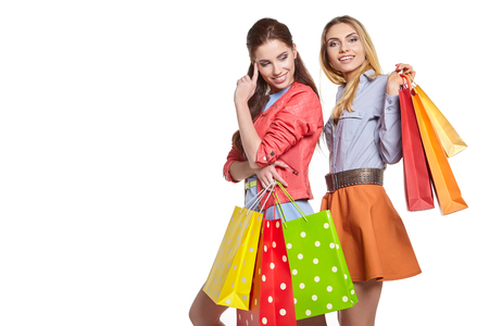 studio image of two beautiful young women, holding a few shopping bags, smiling and looking happy Stock Photo