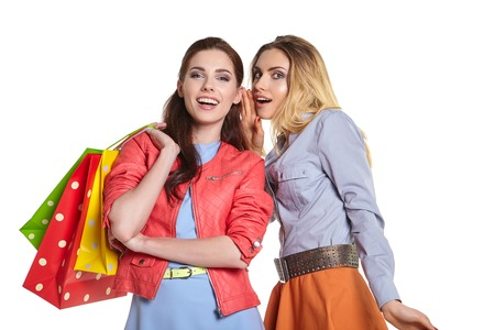 people laughing: shopping, sale and gifts concept - two smiling teenage girls with shopping bags