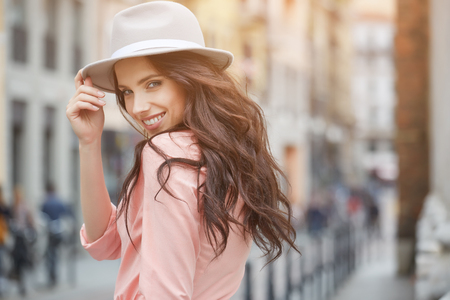 glowing skin: Close-up Fashion woman portrait of young pretty trendy girl posing at the city in Europe,summer street fashion,holding retro fedora hat popular until the 60s.laughing and smiling portrait.trendy