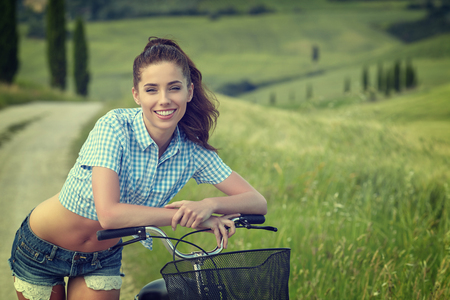 vintage landscape: beautiful girl with vintage bike outdoor, summer Tuscany  time Stock Photo