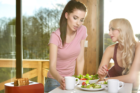 mate drink: Two Female Friends Enjoying Breakfast At Home Together Stock Photo