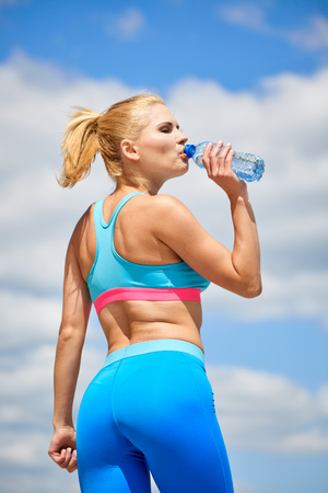 blonde fitness woman drinking water after complete outdoor workout