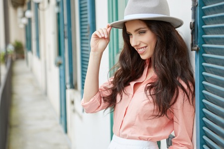 fashionably: Fashionably dressed woman on the house of a Italian town Stock Photo
