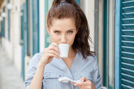 espresso: Woman drinking coffee at terrace on a sunny morning