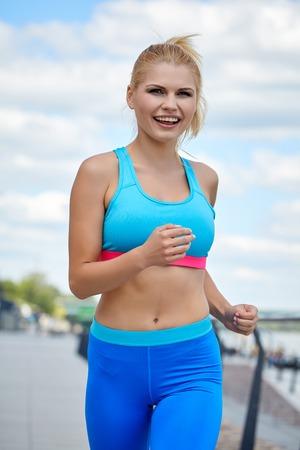 ropa deportiva: ropa deportiva femenina atleta femenina físico delgado ajuste atlético río al aire libre de la ciudad Foto de archivo