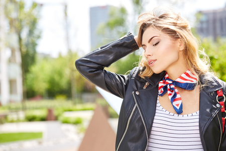 urban fashion: Young urban professional woman in walking in city. Fashion girl living city lifestyle in leather jacket in autumn fall. Trendy modern female.