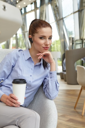 luggage travel: Coffee break. Pleasant modern attractive young woman holding mobile phone and sitting at the table while relaxing in the cafe Stock Photo