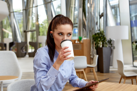 millennial: Young businesswoman drinking coffee and using tablet computer in cafe Stock Photo