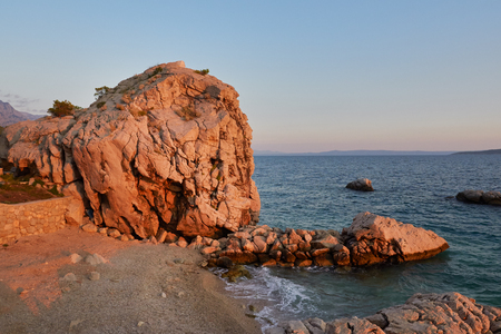 blue sea: Rock island at sunset in small mediterranean town Brela , Croatia