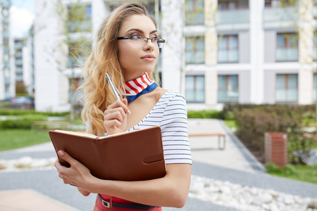 glass brick: Young attractive happy student woman wearing  glasses holding a briefcase Stock Photo