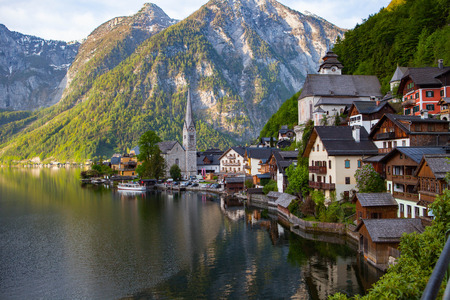 austrian village: Scenic picture-postcard view of famous Hallstatt mountain village with Hallstatter See in the Austrian Alps in beautiful golden morning light in fall, region of Salzkammergut, Austria Stock Photo