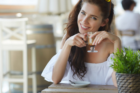 having breakfast: Portrait of beautiful blond woman sitting in outdoors cafe in Italy, drinking coffee