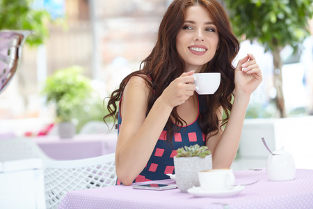 drinks on bar: woman thinking in a coffee shop terrace in the street Stock Photo