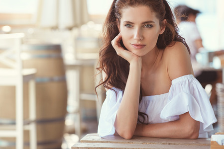 relaxing at home: Portrait of beautiful girl on the summer restaurant