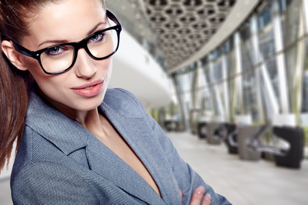 office environment: Portrait of a cute young business woman smiling, in an office environment Stock Photo