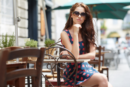 summer dress: Stylish woman, wearing summer dress,  posing at city cafe terrace Stock Photo