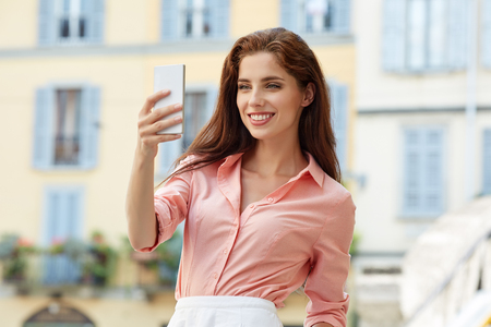 mooie vrouwen: Beautiful brunette business woman photographing selfie on a tablet in her hands outdoors. Stockfoto