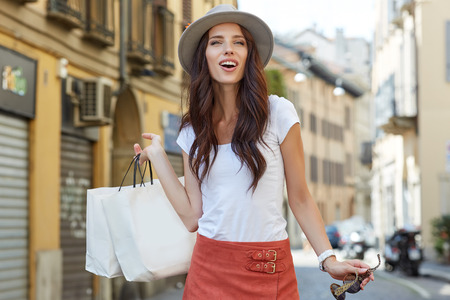 Beautiful happy girl goes shopping in the city.
