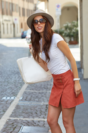 Beautiful brunette young woman tourist  walking on the street Stock Photo - 60105555
