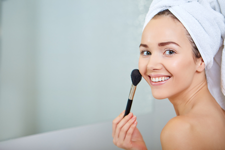 brush in: Beauty woman applying makeup. Beautiful girl looking in the mirror and applying cosmetic with a big brush.