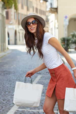 overspending: Young beautiful woman with shopping bags in the ctiy- Lets go shopping concept