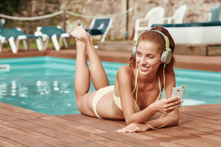 girl lying: Portrait of beautiful girl listening to music in the swimming pool. Stock Photo