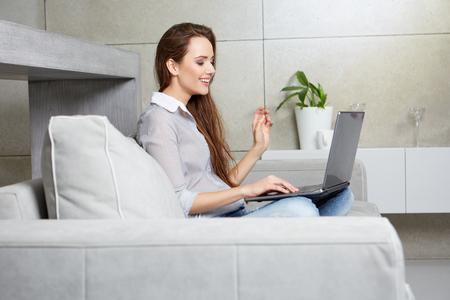 mujer sola: Mujer que usa un ordenador portátil mientras se relaja en el sofá Foto de archivo