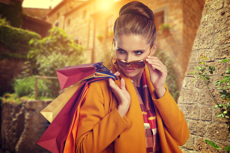 overspending: Young beautiful woman with shopping bags in the city- Lets go shopping concept Stock Photo