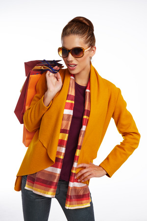 Woman wearing autumn overcoat and scarf  holding shopping bag. Stock Photo