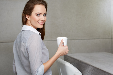 legs folded: A woman sitting on the couch with a cup in her hands and smiling Stock Photo