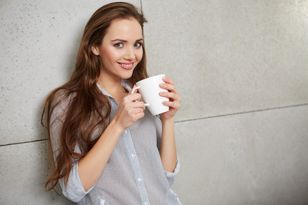 women coffee: A woman sitting on the couch with a cup in her hands and smiling Stock Photo