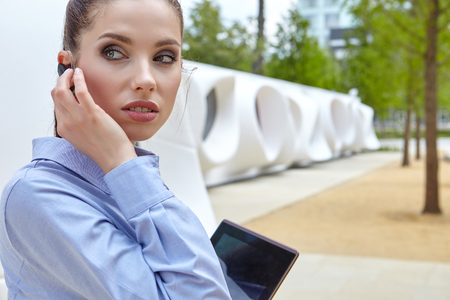 electronic tablet: Smiling businesswoman using electronic tablet outside Stock Photo