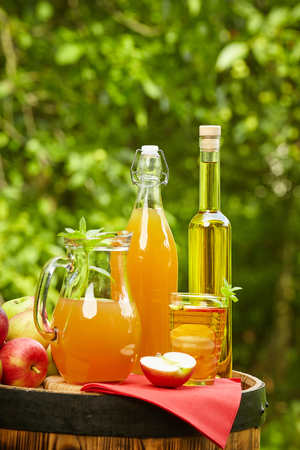 canasta de frutas: Apples and apple preserves on a barrel on the background of the orchard