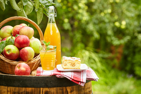 Apples and apple preserves on a barrel on the background of the orchard