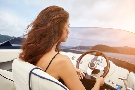 deportes nauticos: Summer vacation - young woman driving a motor boat
