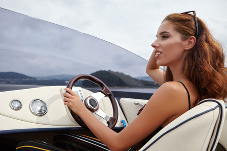 woman young: Summer vacation - young woman driving a motor boat