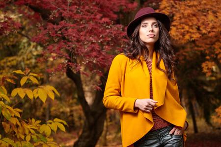 mujer elegante: Hermosa mujer elegante de pie en un parque en otoño, el concepto de la caída
