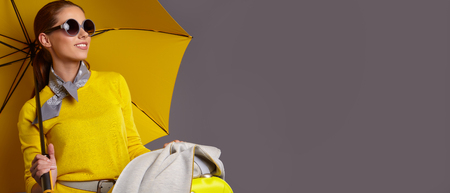 Fashion  woman with yellow umbrella and suitcase. banner concept