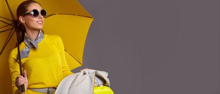 Mode vrouw met gele paraplu en koffer. banner concept