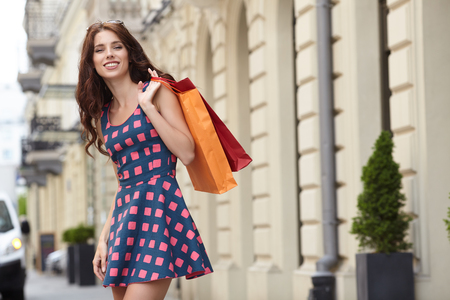 travel woman: Young beautiful woman with shopping bags in the ctiy- Lets go shopping concept