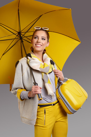 isolated woman: Glamour woman with yellow umbrella and suitcase