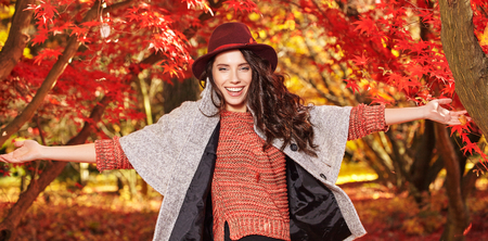 fashion clothing: Fashion woman on a background of red and yellow autumn leaves Stock Photo