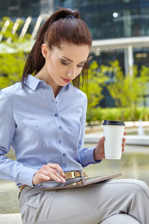 take time out: Woman enjoying coffee outside the office building